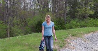 Girl walking by in grass near woods 4k