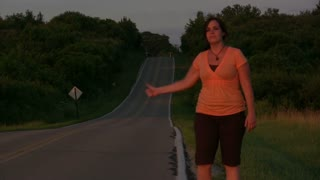 Girl walking down road hitch hiking