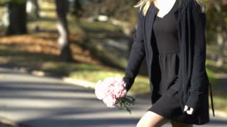 Girl walks up to grave and drops off flowers 4k