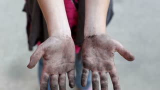 Girl with Dirty Hands showing to camera