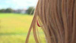 Girl with glasses looking into green field slow motion