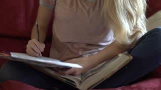 Girl works on homework tilt to face reveal 4k