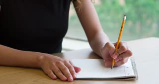Girl writing in notepad with pencil while doing homework 4k