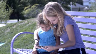 Girls sitting on park bench watching video on cell phone 4k
