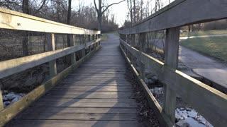 Going across bridge in park at sunset 4k