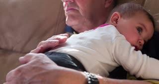 Grandpa holding child on lap while watching TV tilt 4k