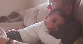 Granpa and baby laying on couch in sunshine pan 4k