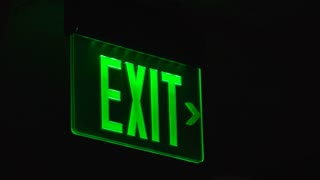 Green exit sign in dark showing way out of building 4k
