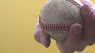 Hand holding baseball in rays of light
