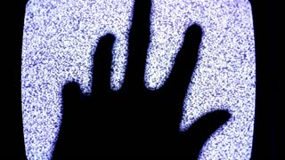 Hand in front of static television screen