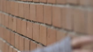 Hand of girl rubbing down brick wall in slow motion