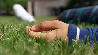 Hand of person laying in grass relaxing 4k
