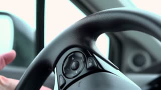Hand of person turning steering wheel slow motion