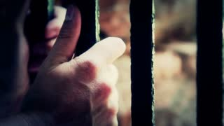 Hands gripping prison bars dramatic lighting
