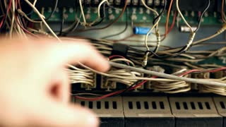 Hands moving wires in electrical control box