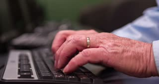 Hands of elderly man using computer at desk 4k