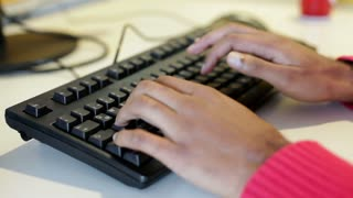 Hands of Indian male typing at computer keyboard.