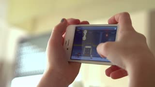 Hands of young girl playing game on iPhone