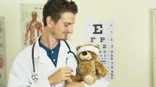 Happy doctor with Teddy bear in arm