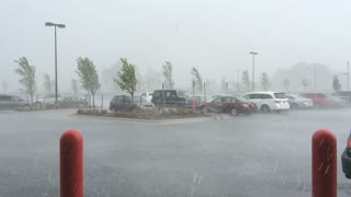 Heavy rain storm with cars in parking lot