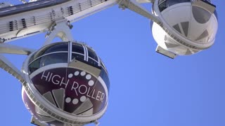 High Roller ride with passengers in pod on blue sky 4k
