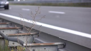 Highway guide rail with traffic going by in background 4k