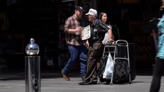 Homeless elderly man standing on Fremont street with sign 4k