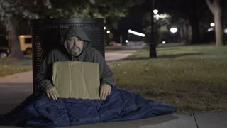 Homeless man in outdoor cold sitting on sidewalk 4k