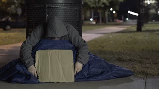 Homeless man keeping head down with cardboard sign at night 4k