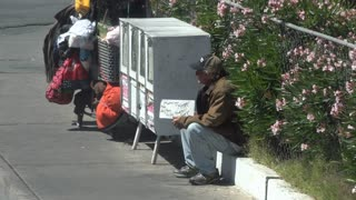 Homeless man sitting on curb with sign 4k