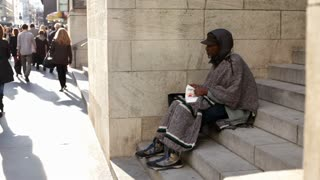 Homeless man sitting on steps in NYC