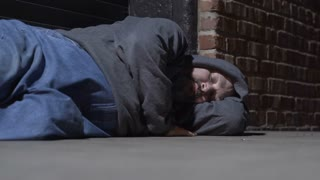 Homeless man sleeping in alley of side street at night 4k