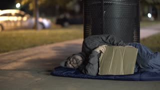Homeless man startled while sleeping on sidewalk at night