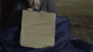 Homeless man with cardboard sign looking at camera 4k