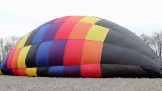 hot air balloon being filled in field