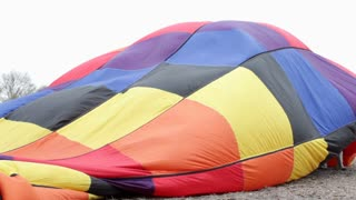 Hot air balloon fabric blowing in wind on ground