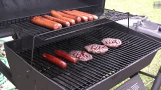Hot dogs being turned on Grill.