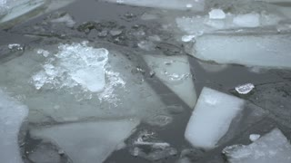 Ice chunks floating by in water close up
