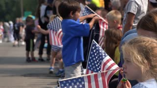 July 4th crowd waiting for parade with flags 4k