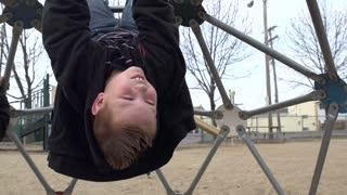 Kid hanging on playground equipment