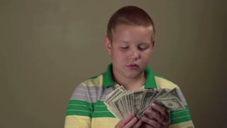 Kid with lots of one dollar bills smiling