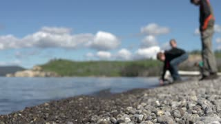 Kids collecting rocks to skip on lake shore