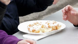 Kids eating Funnel cake at carnival