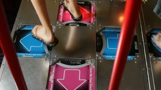 Kids feet playing dancing arcade game