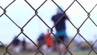 Kids on Football Field focus on fence