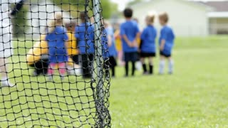 Kids Soccer Game from behind goal net