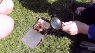 kids using magnifying glass to start fire
