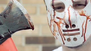 Killer holding bloody ax and wearing mask slow motion