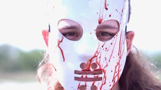 Killer with bloody mask looking at camera slow motion