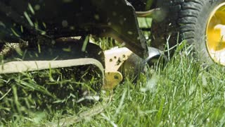 Lawn mower blades cutting grass in slow motion